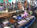 People eating at tables the fish that a woman cooks in her boat at the Taling Chan Floating Market in Bangkok Royalty Free Stock Photo