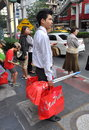 Bangkok thailand thai man with shopping bags young carrying bright red central chitlom waiting to cross sukhamvit road in Royalty Free Stock Images
