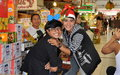 Bangkok thailand two youths at market hall playful thai boys sporting christmas hats ham it up the or tor kor in Stock Photos