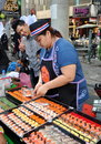 Bangkok thailand woman selling street food thai from a table display on silom road in Royalty Free Stock Photo