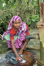 Bangladeshi woman wash clothes at water pump the is squatting down the with a bar of soap to laundry she is dressed in traditional Royalty Free Stock Images