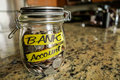 Bank account money jar a clear glass filed with coins and bills saving the words written on the outside Stock Images
