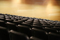 Bank of empty seats in an auditorium for a live stage performance with spotlights shining through the smoky atmosphere Royalty Free Stock Photography