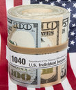 Banknote roll form rubber band american flag the concept of an irs income tax payment using paper bills and a is shown with this Stock Image