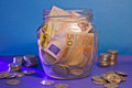 Banknotes and coins in a glass jar euro surrounded by ruble Royalty Free Stock Image
