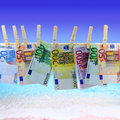 Banknotes in front of the beach hanging on clothesline Stock Photos