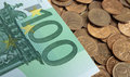 Banknotes of one hundred euros on coins Royalty Free Stock Photography