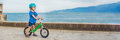 BANNER Active blond kid boy driving bicycle in the park near the sea. Toddler child dreaming and having fun on warm summer day. ou Royalty Free Stock Photo