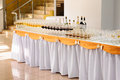 Banquet table with alcohol drinks and rows of stemware Royalty Free Stock Photos