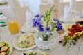 Banquet table in the center of a round with a vase of blue wildflowers Royalty Free Stock Photography