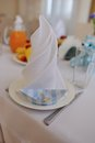 Banquet table close up on a background of a plate with white napkin and paper boats Royalty Free Stock Photos