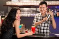 In the bar asian barmen serving drinks to woman Stock Image