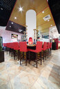 Bar counter with tall red chairs in hall of cozy japanese restaurant Stock Images