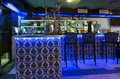 The bar counter with three chairs in cafe illuminated blue light Stock Photography