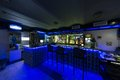 The bar counter with three chairs in cafe illuminated blue light Stock Photo