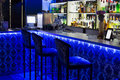 The bar counter with three chairs illuminated blue light Royalty Free Stock Photography
