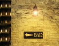 Bar detail of an old stone wall with a signboard that reads and indicates the direction in a yellow light of a lantern and in the Stock Photo