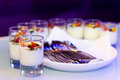 Bar snacks lit by nightclub lights on dark purple background Royalty Free Stock Photo