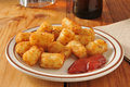Bar snacks a plate of tater tots and catsup served as an appetizer with beer on a counter Royalty Free Stock Photography