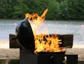 Barbecue grill flames shoot from lakeside Royalty Free Stock Images