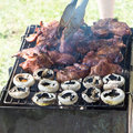Barbecue grilled meat outdoor food meat and mushrooms on plate hands cooking Stock Photos