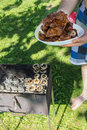 Barbecue grilled meat outdoor food meat and mushrooms on plate hands traditional cooking Royalty Free Stock Images