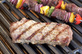 Barbecue. Grilled steak, shish kebab and grilled peppers, onion, on hot grill Royalty Free Stock Photo