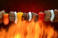 Barbecue kabob over hot fire a steak onion and pepper cooking flames Royalty Free Stock Photos