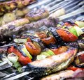 Barbecue meat and fish on skewers with grilled vegetables