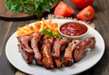 Barbecue pork ribs and vegetables on white plate Royalty Free Stock Photo