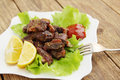 Barbecue spicy fried meat with fresh lettuce leaves Royalty Free Stock Image