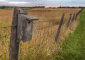 Barbed wire fence birdhouse line leads away into the distance Stock Images