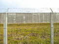 Barbed wire fence and cement wall used for protection construction Royalty Free Stock Images