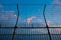 Barbed wire fence silhouettes against cloudy dark blue sky at su Royalty Free Stock Photo
