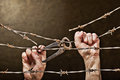 Barbed wire with hands old rusty hand on the dark background Royalty Free Stock Photos