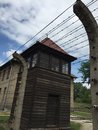 Auschwitz concentration camp guard tower and barbed wire fence Royalty Free Stock Photo