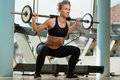 Barbell squat beautiful fit woman doing squats in the gym Royalty Free Stock Photo
