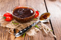 Barbeque sauce with tomatoes smoked salt and fresh herbs on rustic wooden background Royalty Free Stock Photo