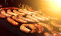 Barbeque summer picnic sausages on the grill with flames and sunlight Stock Photography