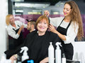 Barber makes the cut for  woman Royalty Free Stock Photo