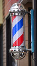 Barber pole sign american with a helical stripe red white and blue on a wall of a s shop Royalty Free Stock Image