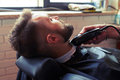 Barber shaving beard with electric razor Royalty Free Stock Photo