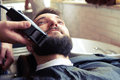Barber shaving beard with electric razor in vintage shop Stock Photos