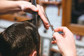 Barbers hands making haircut to man using comb and scissors Royalty Free Stock Photo