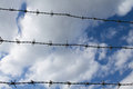 Barbwire fence close up of a on a blue cloudy sky Royalty Free Stock Image