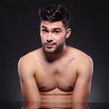 Bare chest young man raises his eyebrows with a looking into the camera with raised while sitting at the desk on a black studio Royalty Free Stock Photography