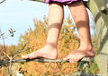 Bare feet on branch of a little kid girl standing thin Stock Image