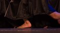 Bare feet of classic dancer in a black skirt satin Royalty Free Stock Photo