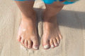 Bare feet little kid stand on the beach, top view Royalty Free Stock Photo