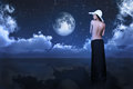 Bare woman looking at moon full between clouds over water Royalty Free Stock Photos
